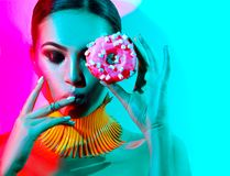 Fashion model woman posing in studio with donut. In colorful bright lights Stock Images