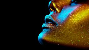 Fashion model woman skin face in bright sparkles, colorful neon lights, beautiful sexy girl lips, mouth. Trendy glowing gold skin royalty free stock image
