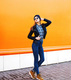 Fashion model woman wearing a rock black style posing over orange Stock Photography