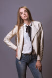 Fashion model woman in white leather coat and jeans.  Royalty Free Stock Images