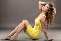 fashion model  yellow dress against gray background Royalty Free Stock Photos