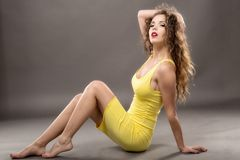Fashion model  yellow dress against gray background Royalty Free Stock Images
