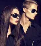 Fashion models couple wearing sunglasses. Over dark background Royalty Free Stock Photography