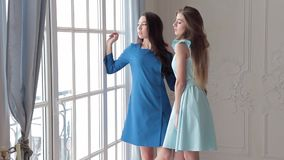 Fashion models in dreses from spring-summer collection posing near window stock footage