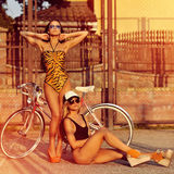 Fashion models in swimsuits posing outdoors near a vintage bike Stock Photo