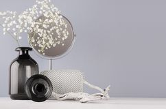 Fashion modern monochrome style in bathroom interior - cosmetic products and accessories, black glass vase with flowers. Fashion modern monochrome style in stock images