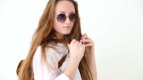 Fashion of modern youth. stylish girl posing against white wall in jeans, white shirt, with leather backpack and glasses. Handheld shoot stock footage