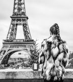 Fashion-monger with Christmas tree in front of Eiffel tower. The Party Season in Paris. Seen from behind modern fashion-monger with Christmas tree in fur coat in Royalty Free Stock Images