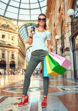 Fashion monger in eyeglasses with shopping bags and coffee cup Stock Photos