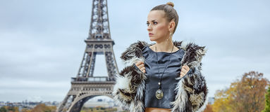Fashion-monger in front of Eiffel tower in Paris looking aside. Bold winter in Paris. trendy fashion-monger in fur coat in the front of Eiffel tower in Paris Stock Photography