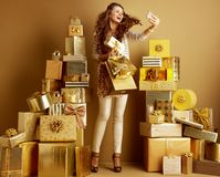 Fashion-monger with gifts and shopping bags taking selfie. Trendy fashion-monger in gold beige clothes with gifts and shopping bags taking selfie with smartphone stock image