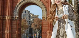 Fashion-monger near Arc de Triomf in Barcelona, writing sms. In Barcelona for a perfect winter. Closeup on smiling trendy fashion-monger in earmuffs near Arc de Royalty Free Stock Images
