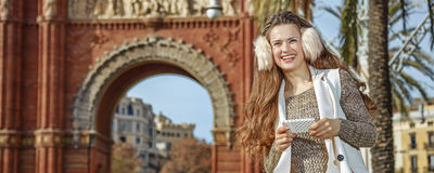 Fashion-monger near Arc de Triomf in Barcelona, writing sms. In Barcelona for a perfect winter. Portrait of smiling trendy fashion-monger in earmuffs near Arc de Royalty Free Stock Images