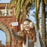 Fashion-monger near Arc de Triomf taking selfie with cellphone Royalty Free Stock Images