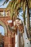 Fashion-monger near Arc de Triomf taking selfie with cellphone Royalty Free Stock Photo