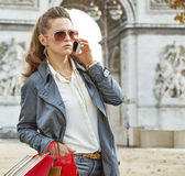 Fashion-monger near Arc de Triomphe in Paris using mobile phone Royalty Free Stock Image