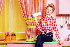Fashion-monger. Pretty girl teenager wearing clothes and hair in pin-up style posing on a pink kitchen. Beauty, youth fashion. Pin-up style royalty free stock image
