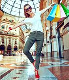 Fashion monger with shopping bags having fun time in Galleria. Discover most unexpected trends in Milan. Full length portrait of happy fashion monger in Royalty Free Stock Photography