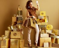 Fashion-monger with shopping bags taking selfie with cellphone. Full length portrait of smiling modern fashion-monger in gold beige pants and brown blouse with royalty free stock images