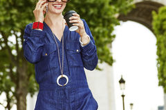 Fashion-monger speaking on mobile while drinking coffee in Paris Stock Photography