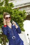 Fashion-monger speaking on mobile while drinking coffee in Paris Stock Photos