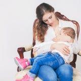 Fashion mother breast feeding a cute baby. Newborn girl. Royalty Free Stock Image
