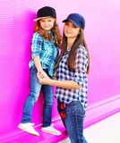 Fashion mother and child little girl in checkered shirts and baseball caps in city on colorful pink wall