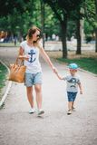 Fashion mother and son walking in a park. Fashion mother and stylish little son walking in a park Royalty Free Stock Photography