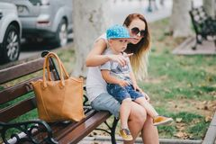 Fashion mother and son walking in a park Royalty Free Stock Images