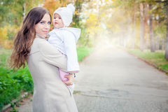 Fashion mother walking with her baby outdoor at autumn park Stock Images
