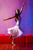 Fashion and movement. Fashion model spinning in white dress on red and blue background Stock Image