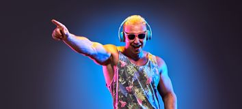 Fashion Muscular DJ. Music nightclub party concept. Fashion Muscular DJ man listen to music in colorful neon light with hand up. Handsome blonde Hipster guy stock images