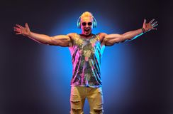 Fashion Muscular DJ. Music nightclub party concept. Fashion Muscular DJ man listen to music in colorful neon light with hands up. Handsome blonde Hipster guy stock image