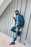 Fashion And Music. Man With Headphones And Phone In City. Fashionable Male Listening Music On Phone In Street. High Resolution Stock Image