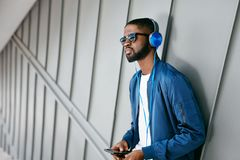 Fashion And Music. Man With Headphones And Phone In City. Fashionable Male Listening Music On Phone In Street. High Resolution Royalty Free Stock Photos