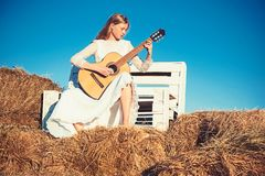 Fashion musician in white dress on sunny nature. Woman guitarist perform music concert. Albino girl hold acoustic guitar. String instrument. Sensual woman play royalty free stock image