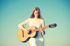 Fashion musician in white dress on sunny nature. Woman guitarist perform music concert. Albino girl hold acoustic guitar. String instrument. Sensual woman play royalty free stock photos