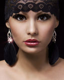 Fashion muslim portrait. Beautiful gypsy young woman with professional makeup and lace accessories over black Royalty Free Stock Images