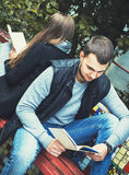 Fashion of nice pretty young hipster woman is sitting back to  with a  handsome man and reading  book. Fashion of nice pretty young hipster women is sitting back Royalty Free Stock Photos