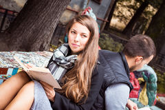 Fashion of nice pretty young hipster woman is sitting back to  with a  handsome man and reading  book. Fashion of nice pretty young hipster women is sitting back Stock Photography