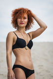 Fashion outdoor photo of beautiful sexy girl with red hair and tanned skin wears black bikini and accessories, relaxing on summer. Beach Royalty Free Stock Photo