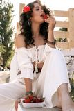 girl with rose in dark curly hair and elegant white outfit, royalty free stock images
