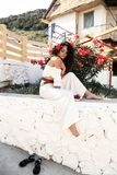 girl with rose in dark curly hair and elegant white outfit, royalty free stock photos