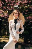 Beautiful woman with blond hair in luxurious wedding dresses with accessories posing in garden with blossoming sakura trees stock images