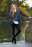 Fashion outdoor photo of beautiful woman wearing coat and leggings posing against the Royalty Free Stock Image