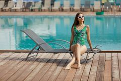 Slim fashion model in a swimsuit posing near the pool Royalty Free Stock Images