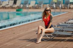 Fashion outdoor photo of gorgeous sexy girl with blond hair in swimsuit relaxing near swimming pool Stock Photography
