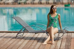Slim fashion model in a swimsuit posing near the pool Stock Photography