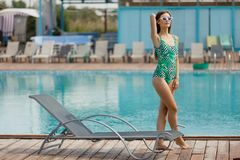 Slim fashion model in a swimsuit posing near the pool Royalty Free Stock Image