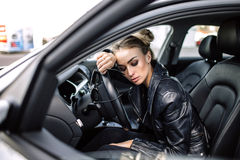 Fashion outdoor photo of sexy beautiful woman with dark hair in black leather jacket and sunglasses posing in luxurious auto Royalty Free Stock Image